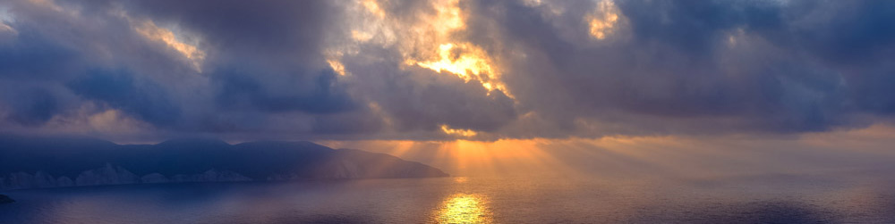 sunset or sunrise over ocean with clouds